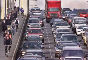 PEDESTRIANS BICYCLES AND CARS CROWD A BRIDGE INTO VANCOUVER