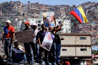 Youth stand in front of their barrio and show love for Hugo Chavez. (Saber y Poder) Image: venezuelanalysis.com